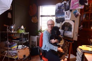 Harriet Cole holding poodle Arthur in her studio.