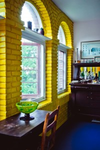 Bright yellow walls pop against a purple floor in James Magruder's solarium.