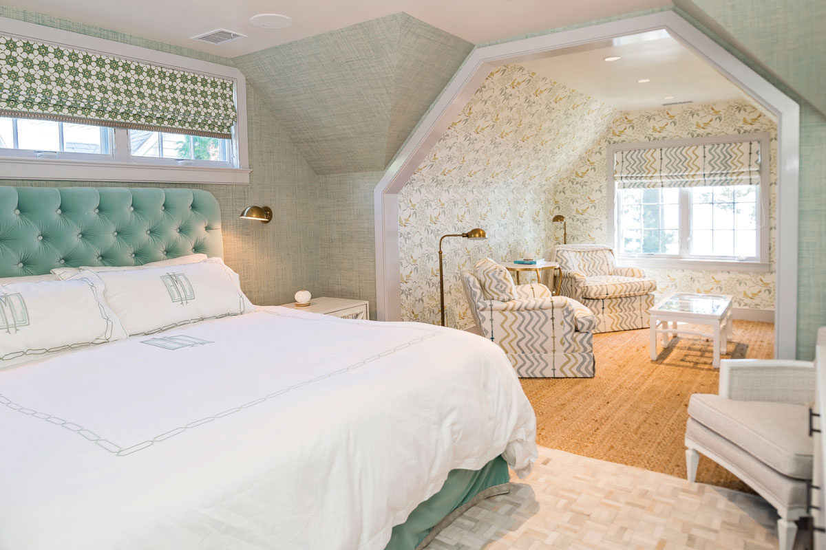 In the master bedroom, a reading alcove sets the stage for a long night's slumber. Custom chairs are covered in Christopher Farr fabric. The shade above the bed is by Galbraith and Paul, with Samuel & Sons taping. Grass cloth wall covering is by Phillip Jeffries.
