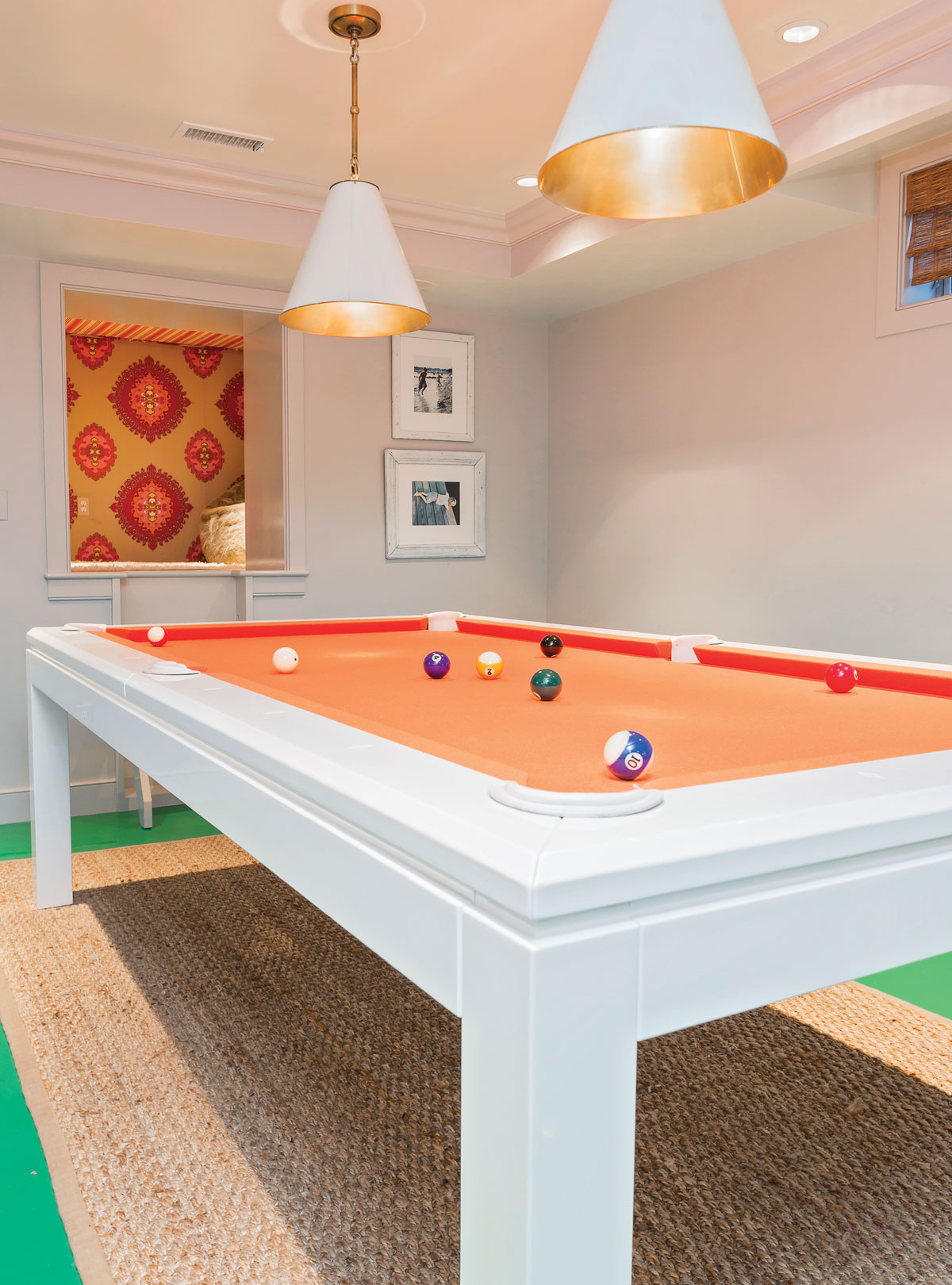 An orange lacquered pool table lives on the green epoxy floor, and a cute custom-created nook overlooks all.