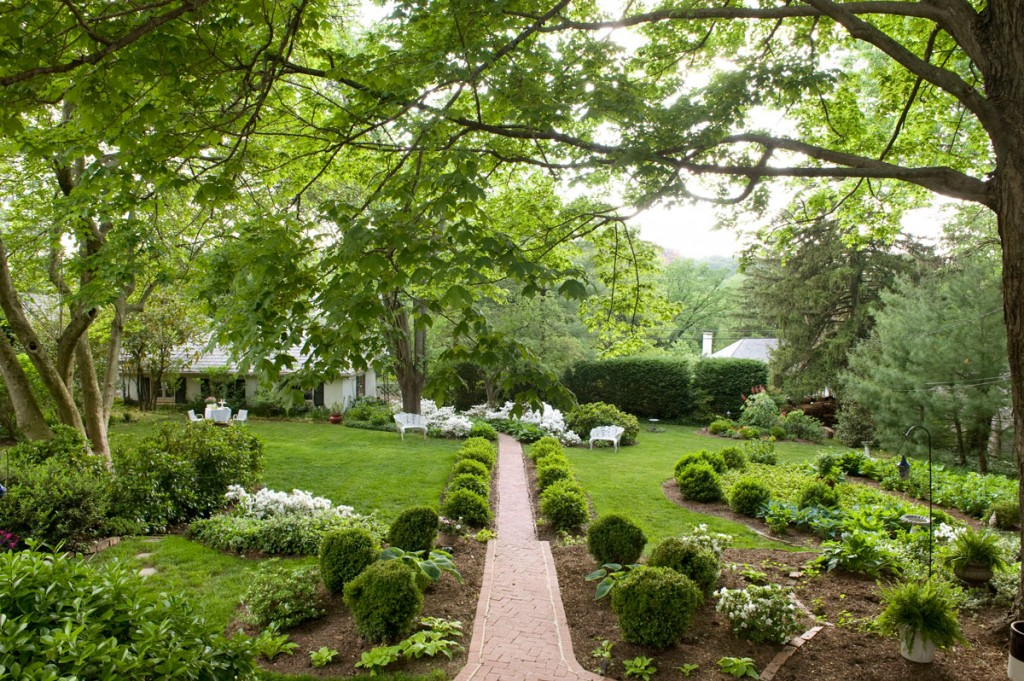 Spring green surrounds the central brick path axis and adjacent serpentine beds edged with boxwoods, hostas and occasional azaleas. An old three-car garage resem-bles an English cottage, gives the back garden a focal point and complements the white of garden furniture and Delaware Valley evergreen azaleas.