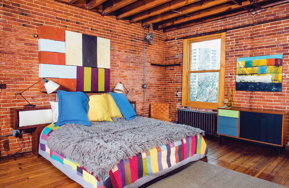In the master bedroom, Lat's colorful wall sculpture—an homage to Sean Scully—hangs above the couple's bed, creating the most colorful area in the house.