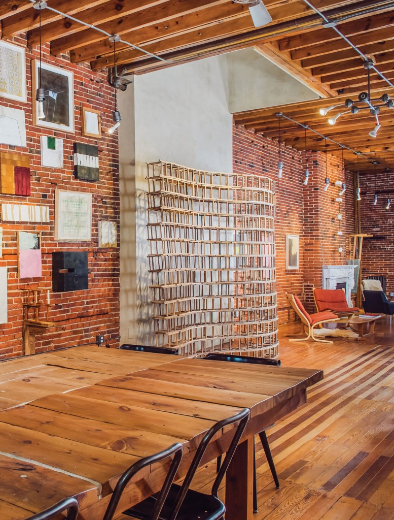 All artwork displayed on the main floor is by Lat Naylor—2007 to 2015. He made the table from wood reclaimed from the house. The piece was originally part of a set of four 14-foot tables made for a 2010 Creative Alliance Art to Dine For Dinner.