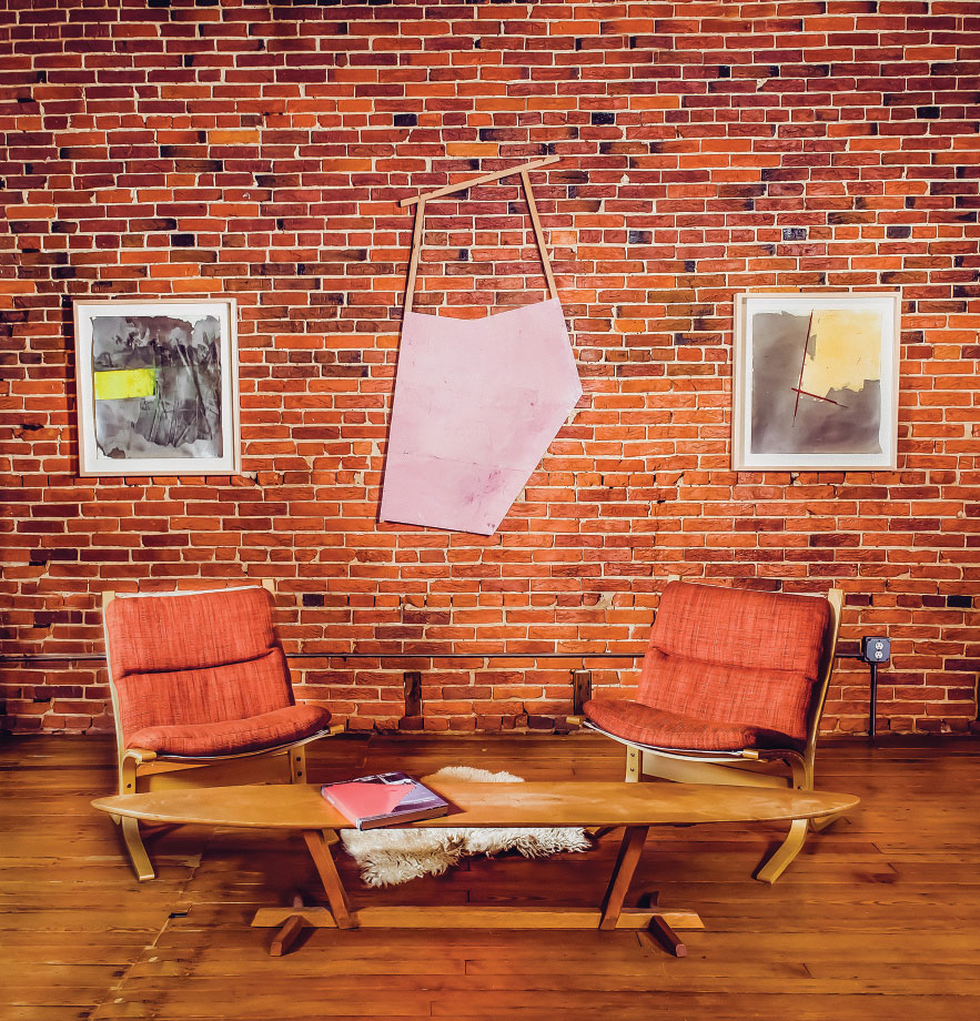 This sitting area is on the main floor just to the right of the entryway. Naylor's work hangs be-hind two Westnofa Siesta Chairs designed by Ingmar Relling, originally made in Norway in 1960s. The table is the work of a California designer.