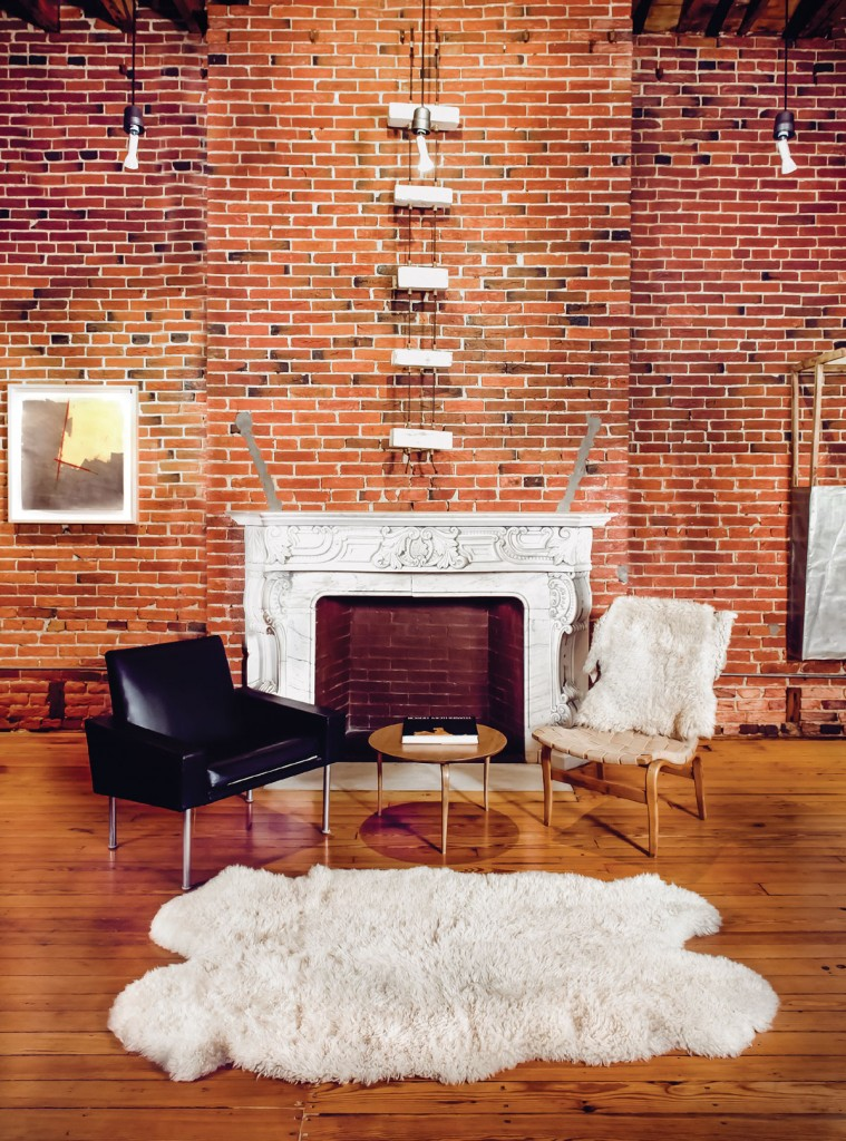 Naylor's artwork, made from materials from the house, hangs in the background. The black chair was designed by Hans Wagner, and the wooden chair is Bruno Mathsson. The rug is made of sheepskin.