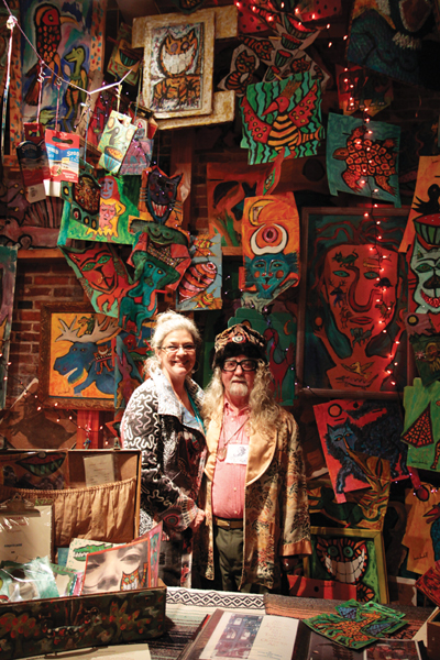 """Alison Spiesman and Brian Dowdall smile in front of Dowdall's """"Wall of Color"""" painting at Bazaart."""