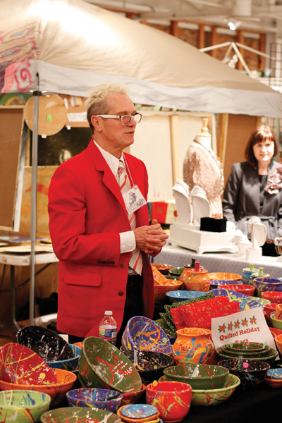 A festively dressed AVAM vendor sells his quilted holiday bags and splatter paint bowls.