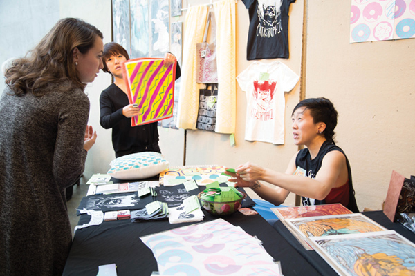 Illustrator Esie Cheng chats with a shopper about her wares and artwork at MICA's Art Market.