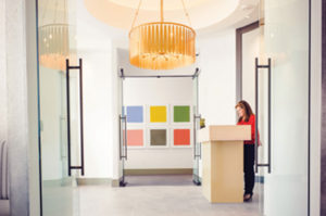 A mid-century-style drum chandelier from Jones Lighting illuminates the entry, a piece by Baltimore artist David Brown in view.