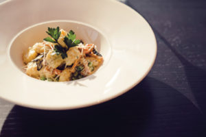 Potato gnocchi with English peas, mushrooms and grano padano