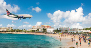 A jet approaches Princess Juliana Airport above onlookers on Maho Beach. The short runway gives beach goers close proximity views of the planes.