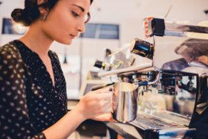 A barista at Café Andamiro  preps a beverage.