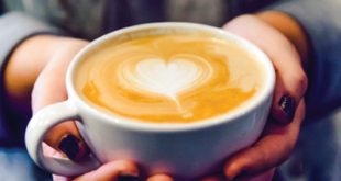A barista at Baby's on Fire serves up a latte with love.